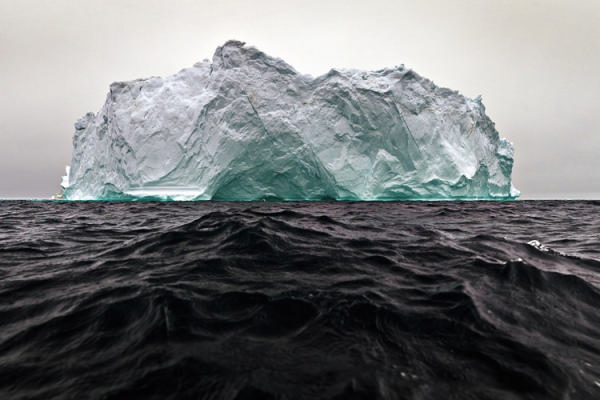 Green iceberg floating in sea.